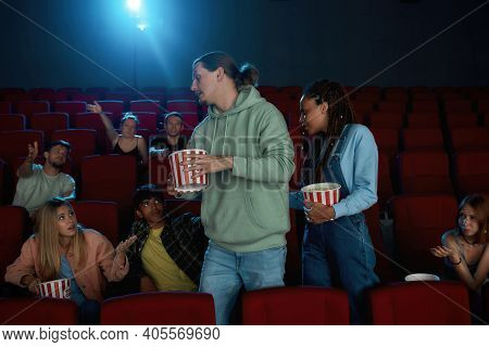Young People, Man And Woman Dislike The Movie, Leaving Cinema Auditorium During The Session. Audienc
