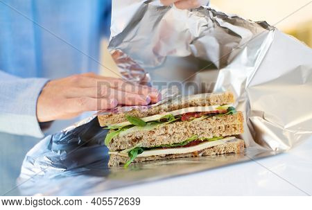 Close Up Of Woman Wrapping Sandwich In Non Reusable Aluminium Foil