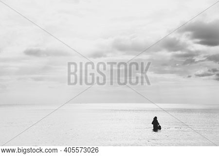 Sea And Sky. People Playing In The Sea Alone Are Lonely. Black And White Photo.