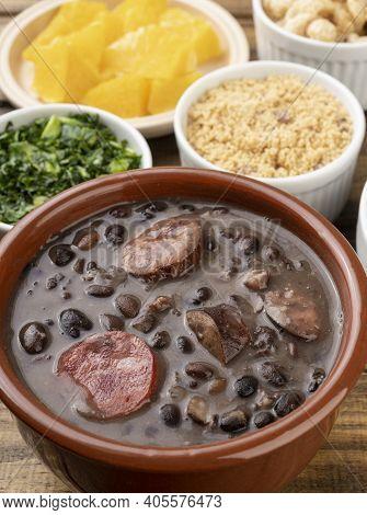 Traditional Brazilian Feijoada With Orange, Kale And Manioc Flour.