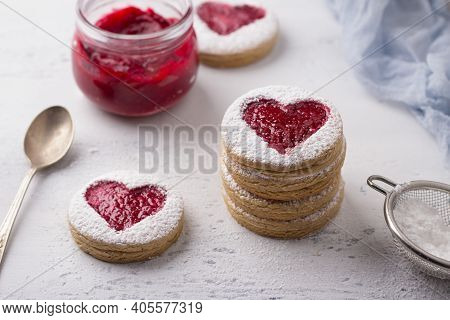 Homemade Shortbread Spicy Cookie With Red Hearts With Jam On White Plate And A Cup Of Coffee  On Gra