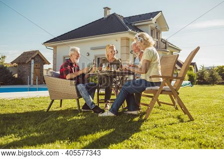 Group Of Cheerful Elderly Friends Having An Outdoor Lunch In The Backyard By The Swimming Pool, Gath