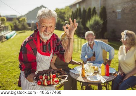 Senior Man Bringing Delicious Food On A Tray While Having An Outdoor Lunch With Friends In The Backy