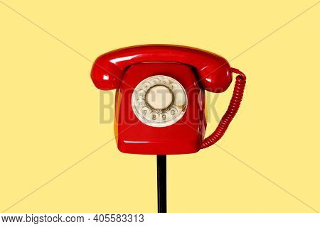 a red landline rotary dial telephone on the top of a black tubular stand, on a yellow background