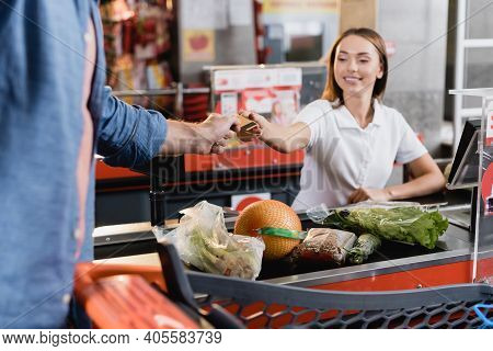 Man Giving Credit Card To Smiling Cashier Near Food On Supermarket Checkout.
