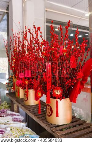 Lucky knot hanging on flower for Chinese new year greeting,middle Chinese character on card means happy new year, character on flower pot and hanging lucky knot mean:good bless for new year