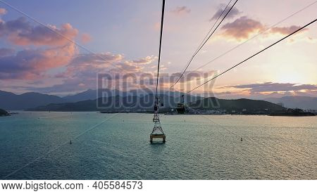 The Cable Car Supports Are Installed In The Bay. The Cabins Move Above The Water Surface. Mountains