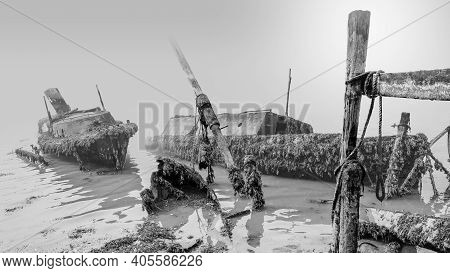Beached Shipwrecks, Covered In Seaweed, Lay In The Shallow Water On A Cold And Misty Morning In Sout