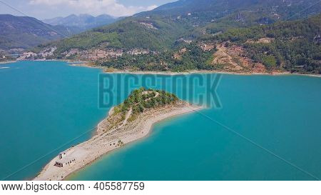 Top View Of Beautiful Cape In Turquoise Lake In Mountains. Clip. Long Promontory Stretches To Middle
