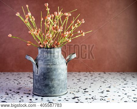 Rustic Metal Milk Can Filled With Orange Artificial Flower Buds On A Terrazzo Counter With A Terra-c