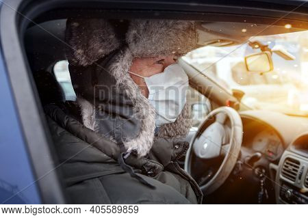 Man In A Fur Hat Cleans Snow From The Roof Of A Car Outdoors On A Winter Day.