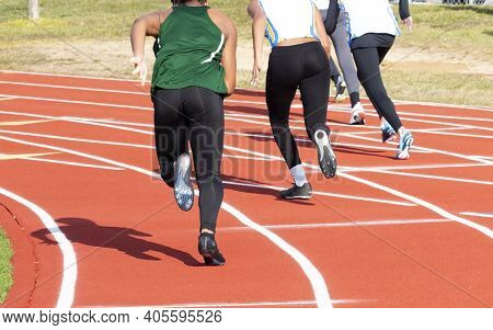 Rear View Of High School Girls Starting A Sprint Race On On Outdoor Track In The Winter.