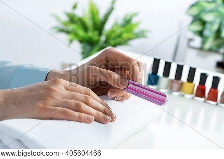 Woman Hand Using Nail File And Create Perfect Nails Shape. Closeup Grinding Female Nails With Nail F