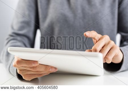 Woman Using Digital Tablet Computer At Office Desk. Close-up Of Female Hand Holding Pen And Touching