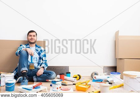 Happy Smiling Caucasian Man Relaxing On Floor. Moving In New House Concept. House Remodeling And Int