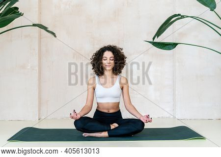 Tranquil Young Afro American Woman Wearing Sportswear, Sitting In Meditation Pose On Exercise Mat At