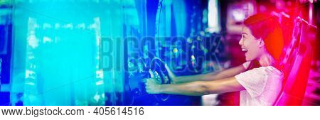 Asian woman playing car racing game at japanese gaming cyber arcade cafe. Driving game machine girl having fun playing racing car videogame driving virtual sports cars simulator banner.