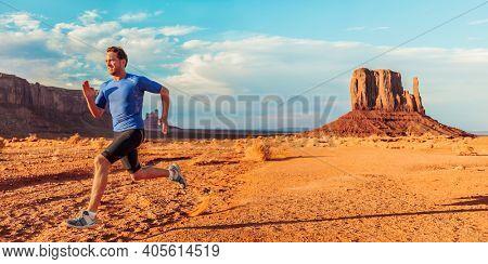 Athlete runner man running across desert mountain landscape on run trail sprinting outdoors. Monument valley, USA banner panoramic. Sport background.