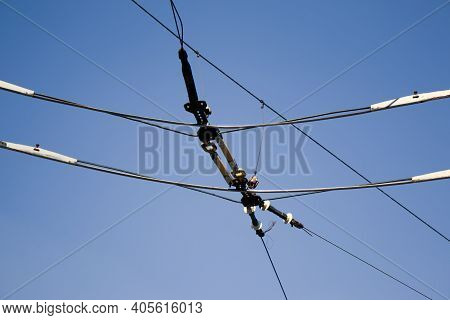 Overhead Electric Transmission Lines Against Blue Sky Background. Industrial Electric Cable Lines Pa