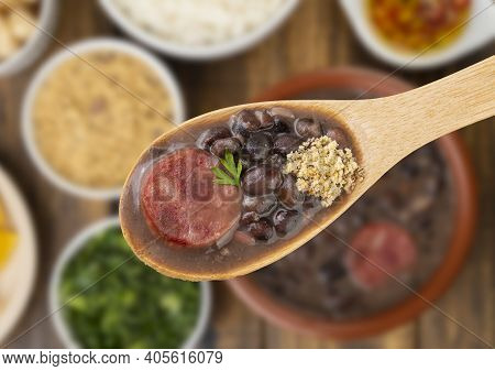 Traditional Brazilian Feijoada In A Spoon Over Unfocused Background.