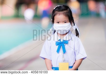 Female Student Wearing White Mask Goes To School. Asian Girl Wear Mask To Prevent The Outbreak Of Ne