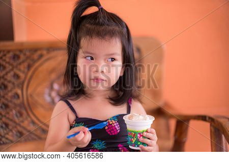 Cute Child Glanced At The Side. Make A Curious Face. Two Hands Holding Spoon Plastic And Ice Cream C