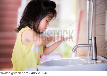 Candid Short One Little Asian Girl Washing Her Hands. She Casually Scrubbed The Soap On Her Two Hand