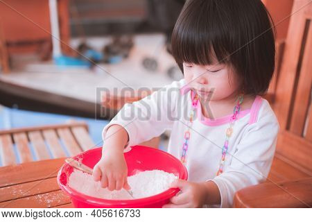One Little Asian Girl Age 2-3 Years Old. She Is Doing Flour Making Patongko Activities. She Was Inte