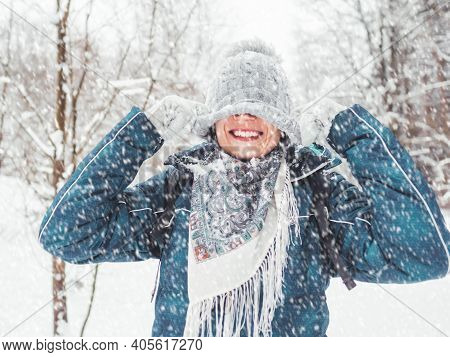 Smiling Woman Is Playing With Knitted Hat. Fun In Snowy Winter Forest. Woman Laughs As She Walks Thr