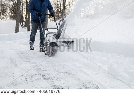 Snow Blower In Action Clearing A Residential Driveway After Snow Storm