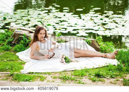 Full body portrait of a young beautiful woman in white dress posing by the lake