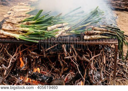 Fresh Ripe Spring Onion Is Grilling On The Big Metal Barbeque On The Market. Traditional Outdoor Hol