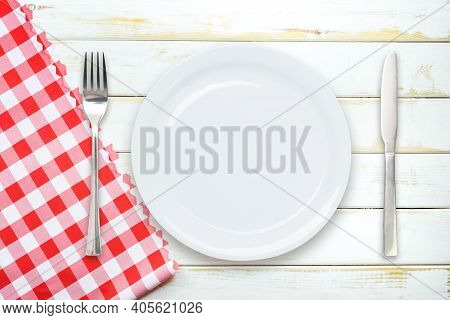 Rustic Italian Cooking Template - Top View Of An Empty Ceramic White Plate With Cutlery On A Wooden