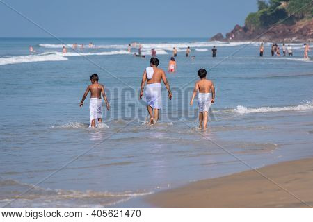 Indian Man And Kids, All Wearing Traditional Swimming Garments, Enjoy The Sea In Varkala, Kerala. Fa