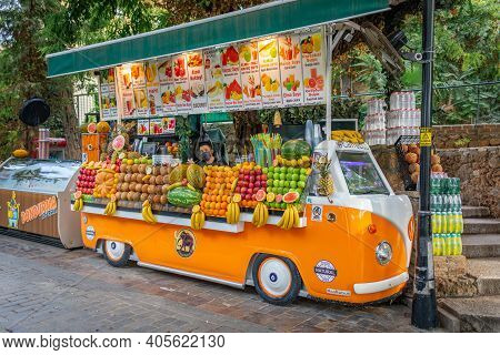 Bright Colorful Fruit Shop In Form Of Volkswagen T1 Car, Symbol Of Hippies, In Port Of Old City, And