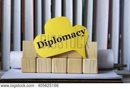 Diplomacy - Word On Yellow Paper Against The Background Of Wooden Cubes And Standing Books. Info Con