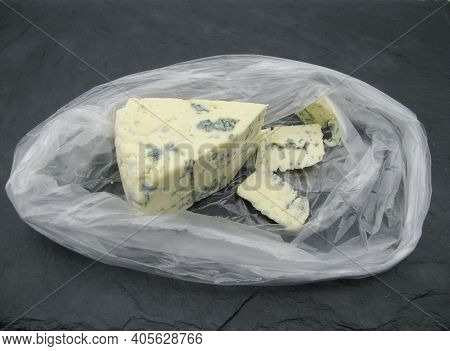 Triangular Sliced Piece Of Cheese With Blue Dorblu Mold In A Transparent Bag.