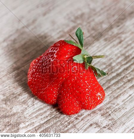 Ugly Strawberry On Wooden Background. Trendy Ugly Food.