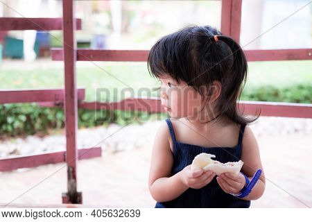 Portrait​ Image​ Of​ 3 Years​ Old​ Baby.​ Hungry Asian​ Child​ Girl​​ Use Her Hand Eating​ Some​ San