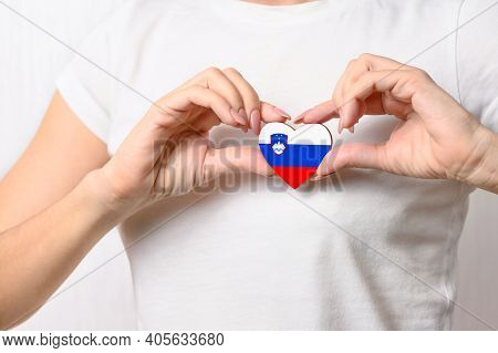 Love Slovenia. A Girl Holds A Heart In The Form Of The Flag Of Slovenia On Her Chest. Slovenian Conc