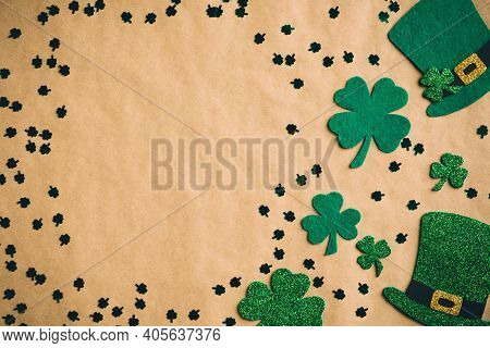 Happy Saint Patrick's Day Concept. Flat Lay Composition With Green Hats And Shamrock Leaves On Kraft