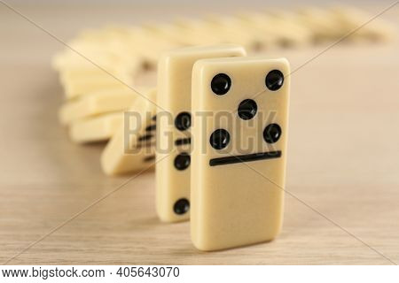 White Domino Tiles Falling On Wooden Table, Closeup