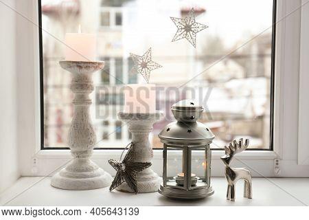 Decorative Christmas Lantern And Candles On Windowsill