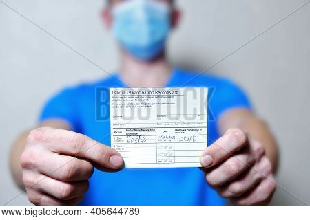 Male Is Holding A Vaccination Record Card And Corona Virus Vaccine Vials. Passport Of Immunity To Th