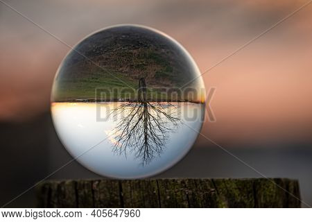 A Lensball Sits Atop A Fencepost, Revealing A Barren Tree In Front Of An Evening Sky.