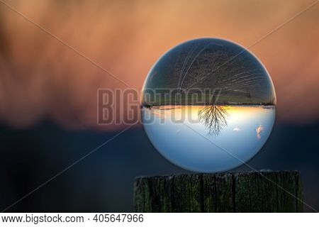 A Lensball Sits Atop A Fencepost, Revealing A Small Barren Tree In Front Of An Evening Sky.