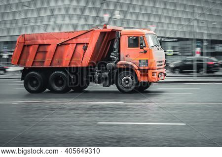 Moscow, Russia - January 29, 2021: Orange Garbage Truck In Motion On City Street. Dump Truck Driving
