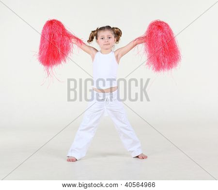 Little barefoot girl with funny hairdo in white clothes holds in raised hands red pompoms and displays star.