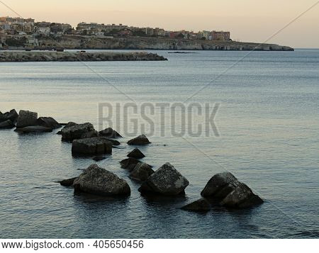 Syracuse From The Sea With Rocks In Foreground, Sicily, Italy