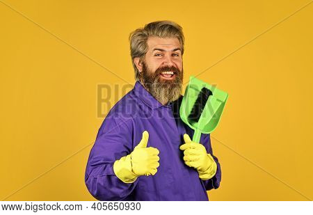 Changing Responsibilities. Male Janitor With Cleaning Supply. Sweeping The Floor. Man Cleaner. Beard